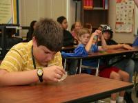 Daniel, a LEAP student, examining a petri dish.