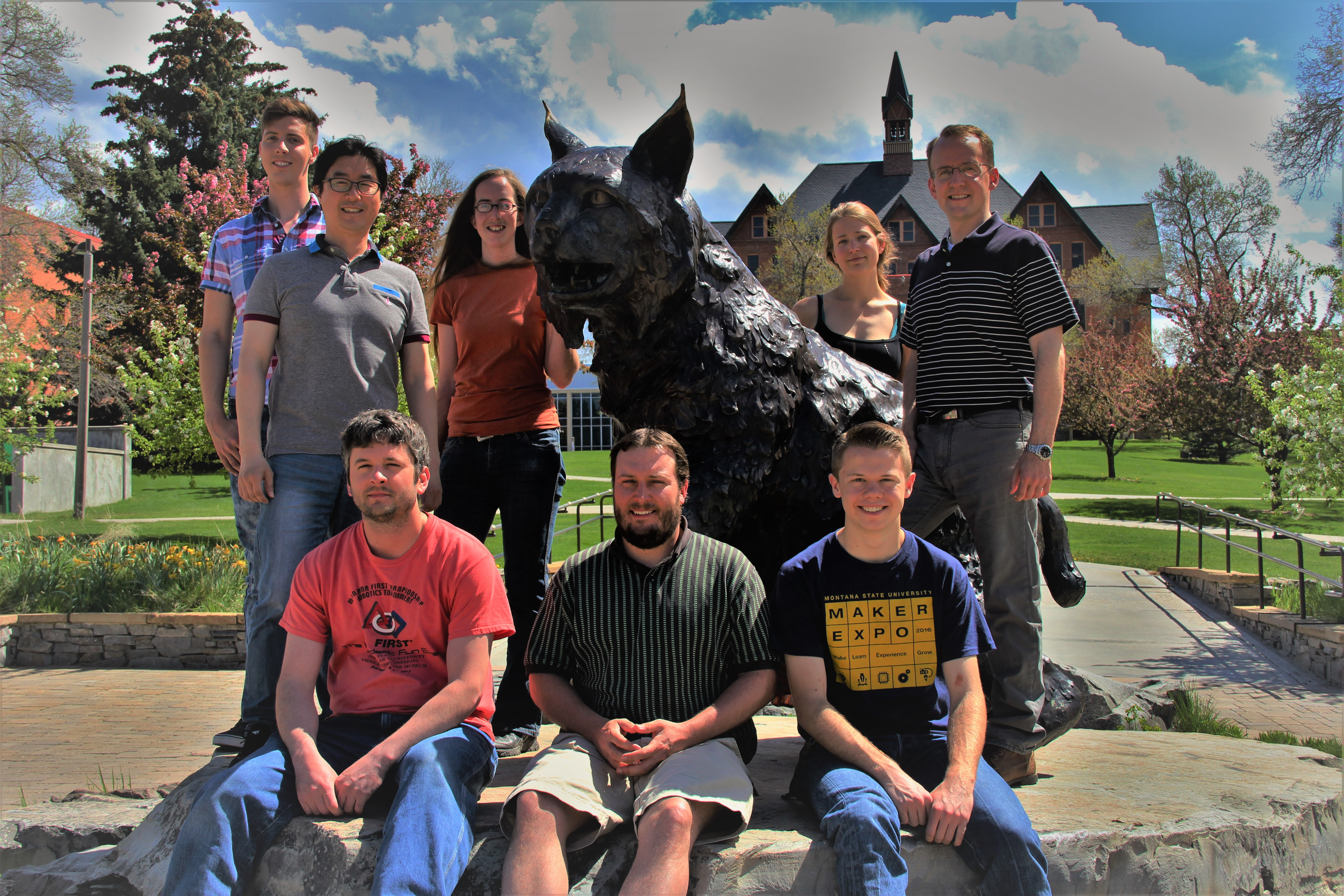 Members of the Biochemical Engineering Lab standing around Spirit the bobcat.